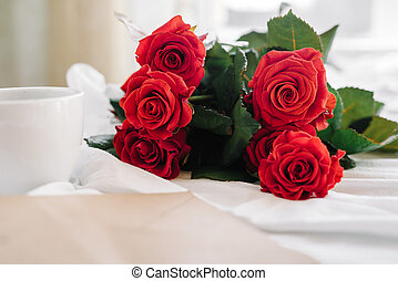 cup of coffee and a bouquet of red roses, envelope