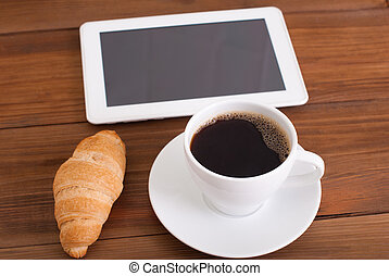 Cup of coffee and a croissant digital tablet on the table.