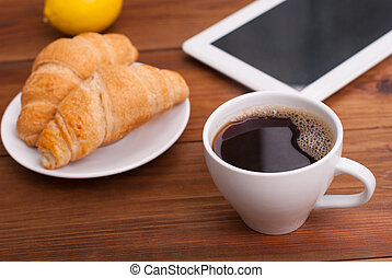 Cup of coffee and a croissant on the table tablet.