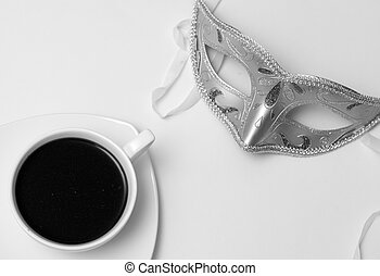 Cup of coffee and a mask on white