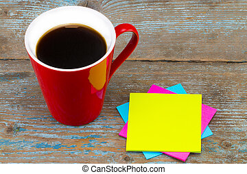 Cup of coffee and a  sticky notes with empty space for a text on wooden background