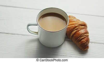 Cup of coffee and baked croissant - From above of white cup...