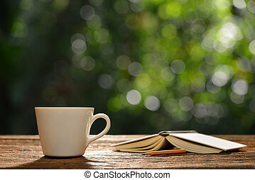 Cup of coffee and book in the garden
