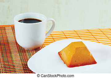 Cup of coffee and caramel pudding on a bamboo table cloth still life