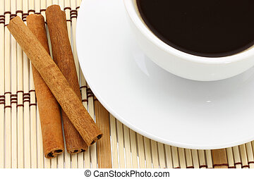 Cup of coffee and cinnamon on wooden background