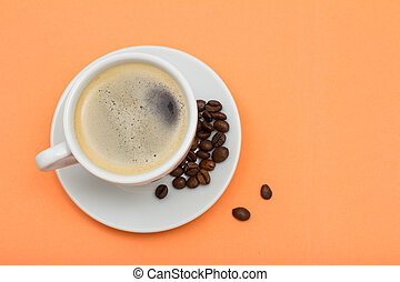 Cup of coffee and coffee beans on peach background