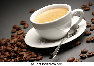 White cup of coffee with froth and coffee beans on dark gray background.