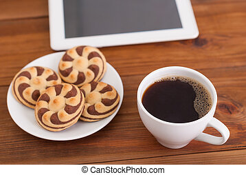 Cup of coffee and cookies a digital tablet on the table.
