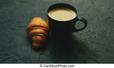 Cup of coffee and croissant - Black mug with coffee and milk...