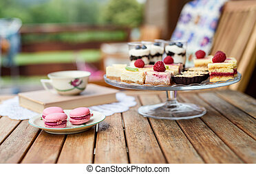 Cup of coffee and desserts on table, close-up.