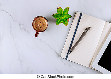 Cup of coffee and digital tablet with notebook, pen, office desk table