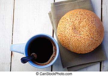 cup of coffee and loaf with sesame