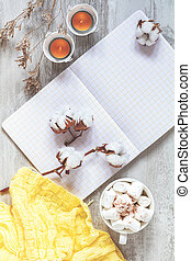 Cup of coffee and marshmallow, candles, cotton plant flower branches, notepad