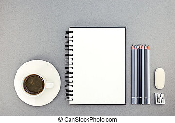 cup of coffee and notebook with drawing tools on desk