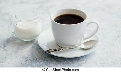 Cup of coffee and pitcher of milk - Arrangement of small...
