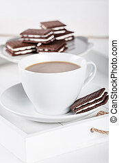 Cup of coffee and plate with cookies on a white tray