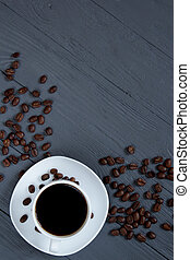 Cup of coffee and scattered coffee beans on wooden surface