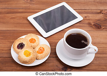 Cup of coffee and sweet cakes digital tablet on the table.