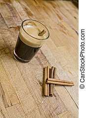 Cup of coffee and three cinnamon sticks