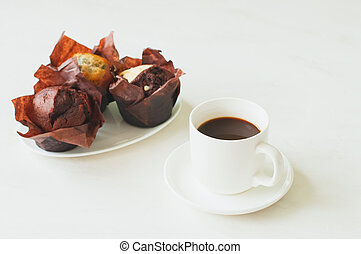 Cup of coffee and three muffins on a white background.