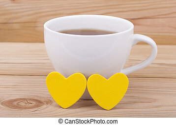 Cup of coffee and two hearts.