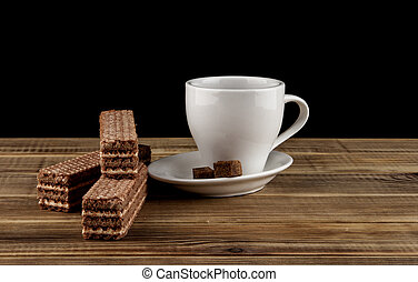 cup of coffee and waffles on a wooden table isolated on a black background