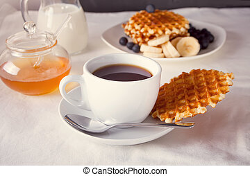 Cup of coffee and waffles with bananas, blueberries and honey.