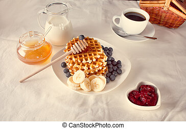 Cup of coffee and waffles with bananas, jam, blueberries and honey.