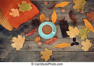 Cup of coffee, autumn leaves and a smartphone on a wooden background. Top view .