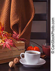 Cup of coffee, autumn leaves, pumpkin, books and sweater on the wooden chair. Autumn concept.