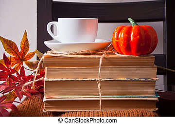 Cup of coffee, autumn leaves, small pumpkin, old books on the wooden black chair. Autumn harvest. Autumn concept