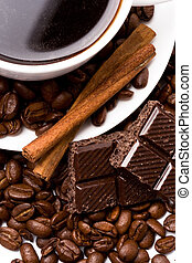 cup of coffee, beans, cinnamon sticks and black chocolate closeup