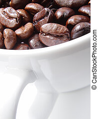 Close up of coffee beans in a white cup.