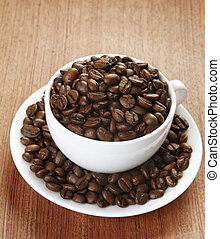 Coffee beans in a cup and saucer on a wooden surface