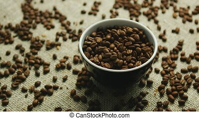 Cup of coffee beans on canvas - Closeup of small brown cup...