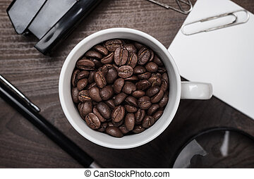 cup of coffee beans on wooden table in the office