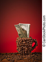 The coffee cup which is made with coffee beans. Dollar bills in the cup.