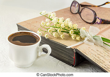 Cup of coffee, book and lily flowers