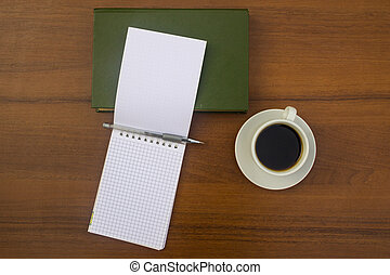 Cup of coffee, book, notepad and pen on wooden desk