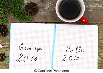 cup of coffee christmas fir tree with cones and notebook with labeled :2019 Hello, goodbye 2018 on wooden background from above