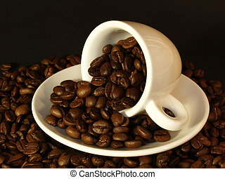 Coffee beans in a white cup lying on a saucer