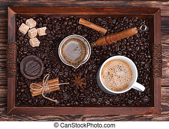 Cup of coffee, coffeepot, biscuit, cinnamon, anise, sugar, coffee beans on a wooden tray.  View from the top.