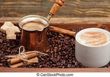 Cup of coffee, coffeepot, cinnamon sticks, anise, sugar, coffee beans on a wooden background