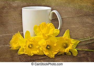 Cup of coffee and daffodils on table outdoors - textured image