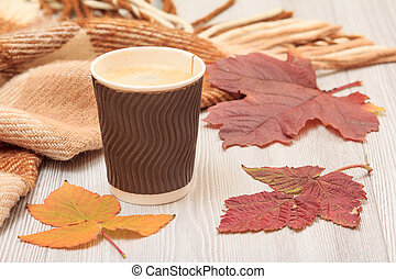 Cup of coffee, checkered wool plaid and dry leaves on gray wooden boards. An autumn still llife.