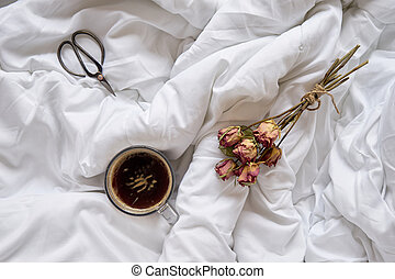 Cup of coffee, dry roses and vintage scissors on bed