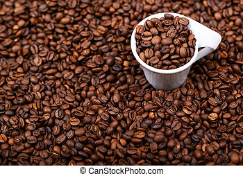 Cup of coffee filled with coffee beans