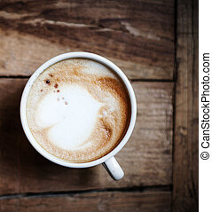 Cup of Coffee for breakfast on rustic wooden table, top view. Cappuccino over wooden background