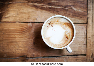 Cup of Coffee for breakfast on rustic wooden table, top view. Cappuccino over wooden background with copy space for text