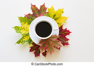 Cup of coffee, framed with autumn leaves on white background. Flat lay. Overhead view